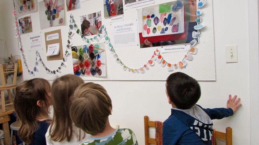 Children looking at documentation of color on wall