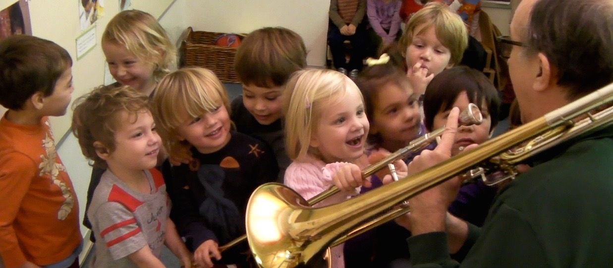 Children playing trombone with a parent