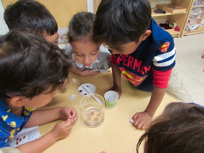 Children looking at a glass of coins in water